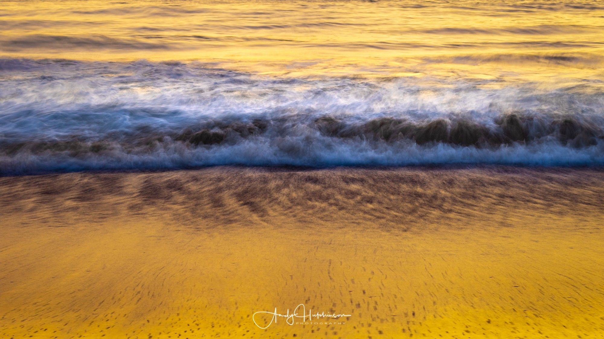 Golden sands lit by the early colour.